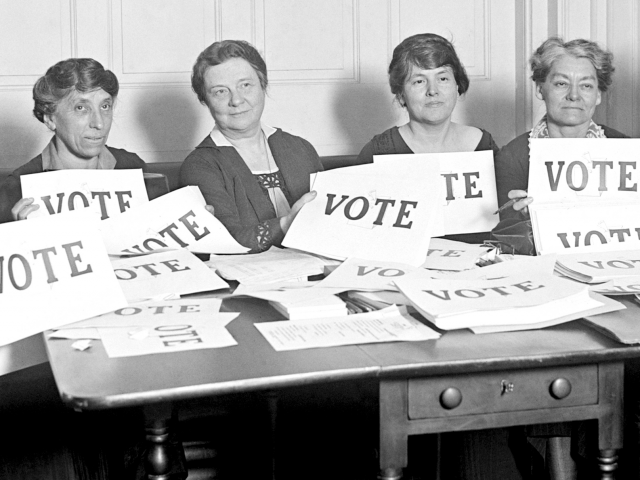 Women holding vote signs