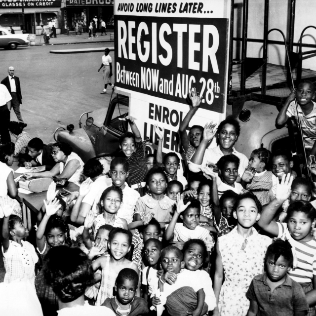 African American children in front of a voter registration table.