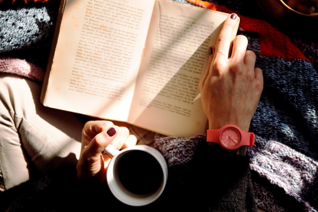 Close up photo of a person reading and drinking coffee