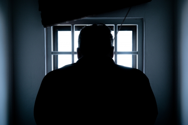 Silhouette of man standing in front of a window