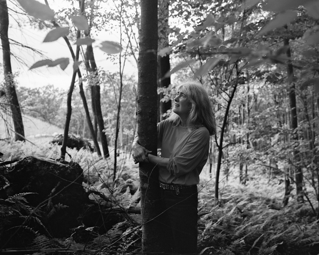woman with her arms around a tree, standing in wooded area