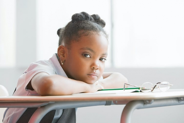 Student sitting at a desk in a school classroom