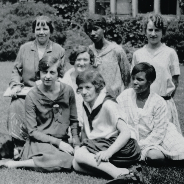 Female students sit on lawn of college campus