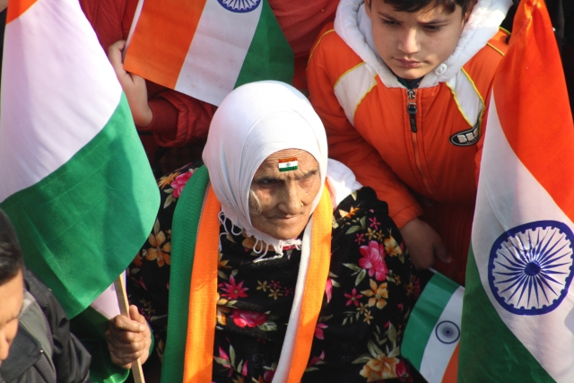 Old woman in a crowd holding an Indian flag
