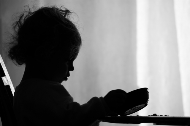 silhouette of child with empty food bowl